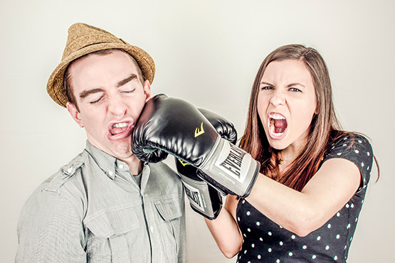 Free Young woman punching man in the face with boxing gloves