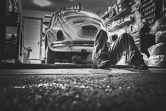 Free Man repairing a vintage car