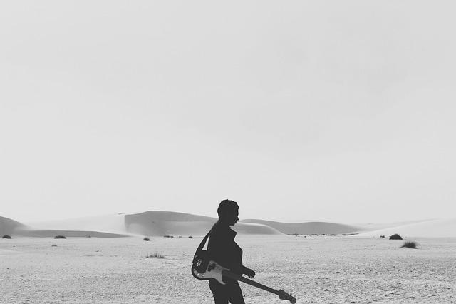 Free guitarist desert sahara walking alone musician