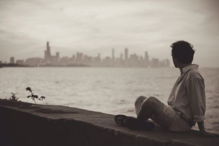 Free Man sitting on stone wall and looking at the city