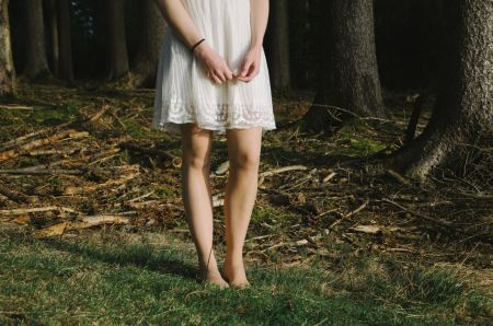 Free Young girl in white dress sitting barefoot in the grass