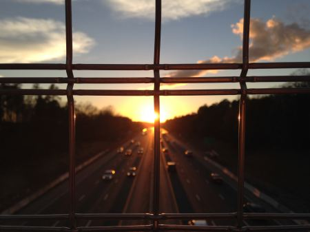 Free Sunset on the highway seen through the bars