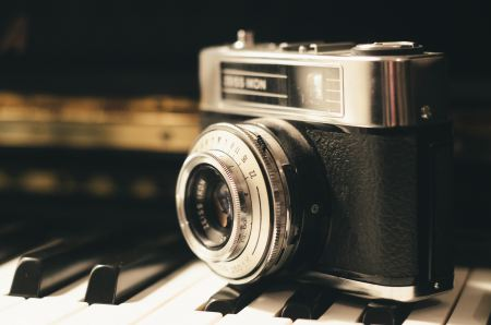 Free Vintage camera sitting on piano keys