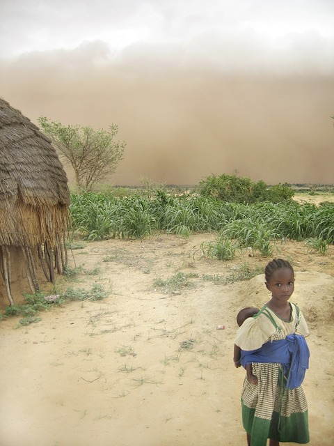 Free niger girl woman baby hut sand sky clouds