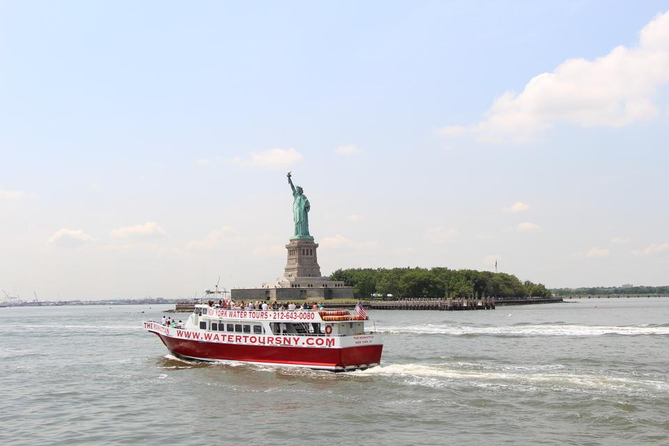 Free The Statue of Liberty and a passenger boat in front
