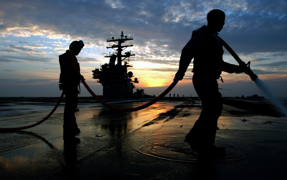 Free Aviation Boatswain's Mates wash down the ships flight deck