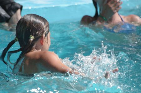 Free young girl swims in the pool