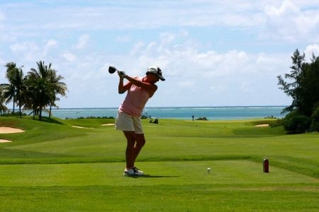 Free Girl golf player with driver teeing-off from tee-box to shoot