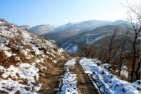 Free Rural unpaved road waving over the hills and mountains on a snowy