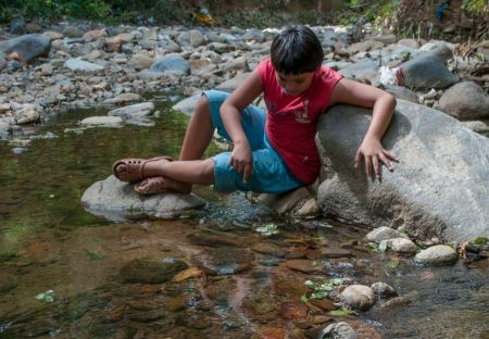 Free boy play with water on the river