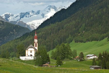 Free Red-steepled church surrounded by alpine