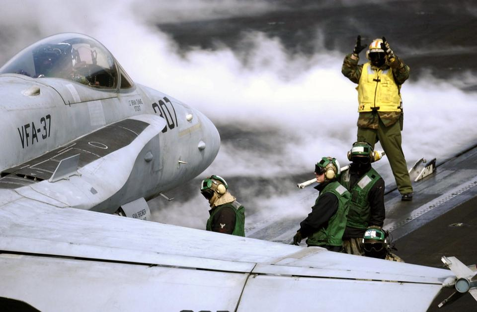 Free Flight deck Sailors position an F-18 Hornet