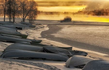 Free Frozen boat on the lake in winter at sunrise