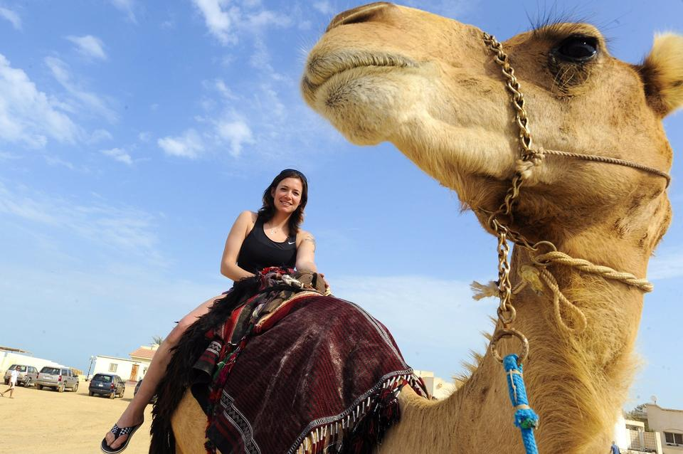 Free Woman tourist during camel ride
