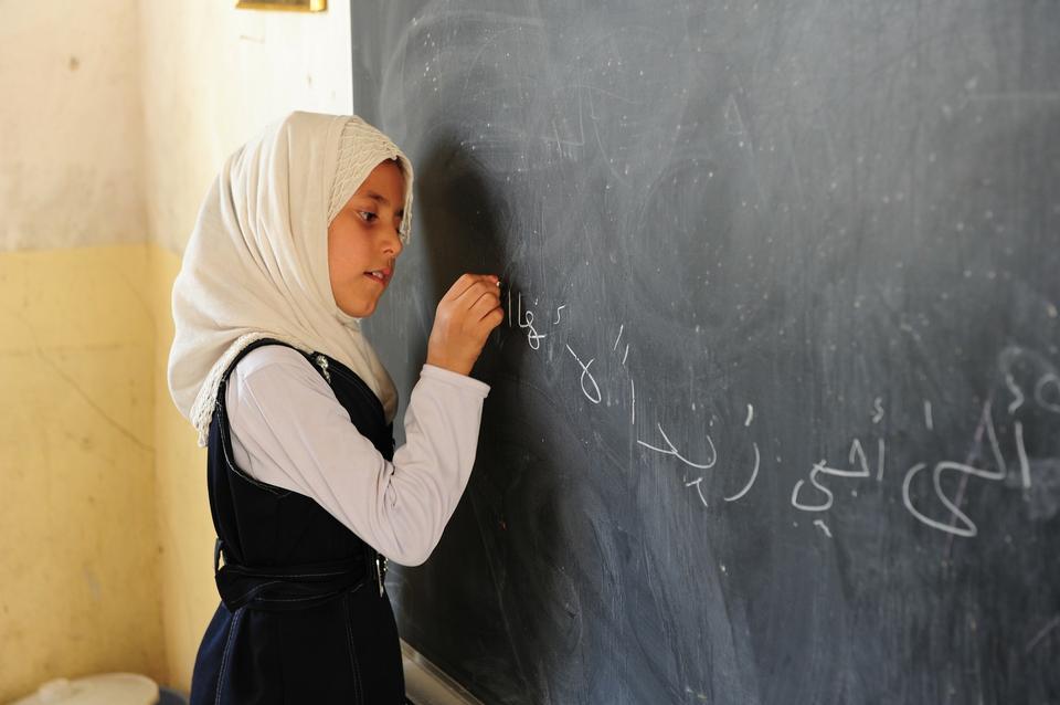 Free Girl writing math equations on a blackboard in class
