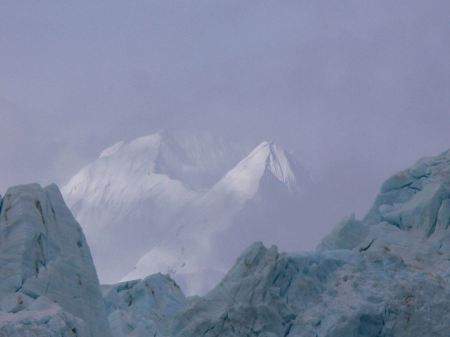 Free Mountains rise through the clouds above a glacier