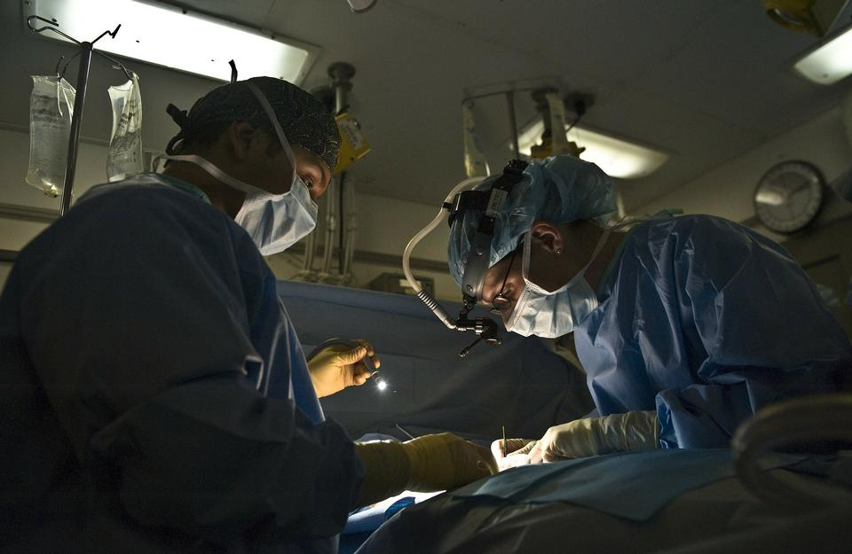 Free Surgeons surrounding patient on operation table