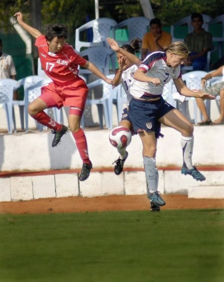 Free Girls heading soccer ball during match against blue sky
