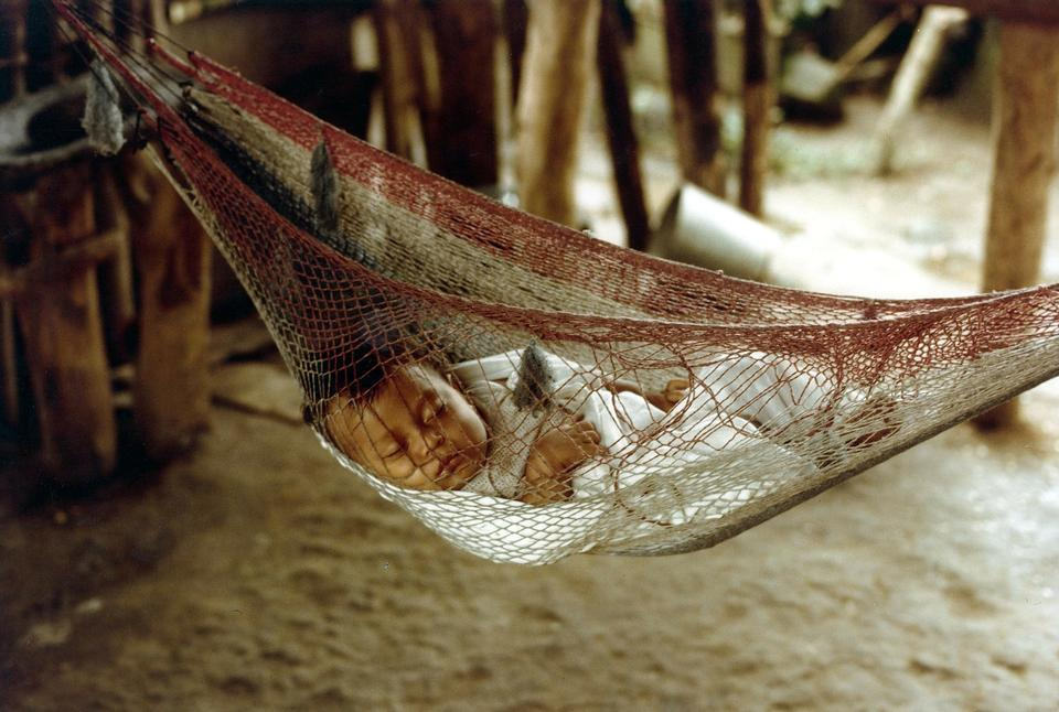 Free Baby sleeping peacefully in striped sling as hammock