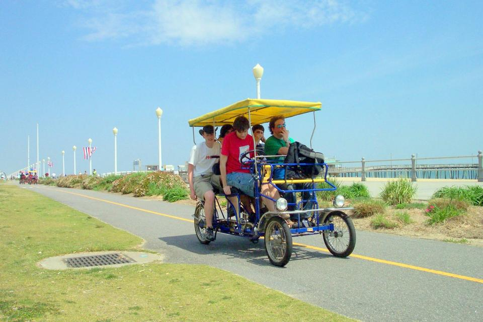 Free People riding a rental surrey on the Boardwalk in Virginia Beach