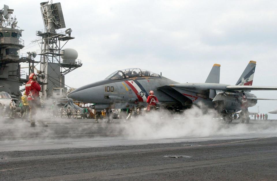 Free A flight deck crewmember guides an F-14D Tomcat