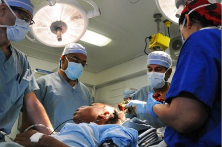 Free Team of surgeon in uniform perform operation on a patient