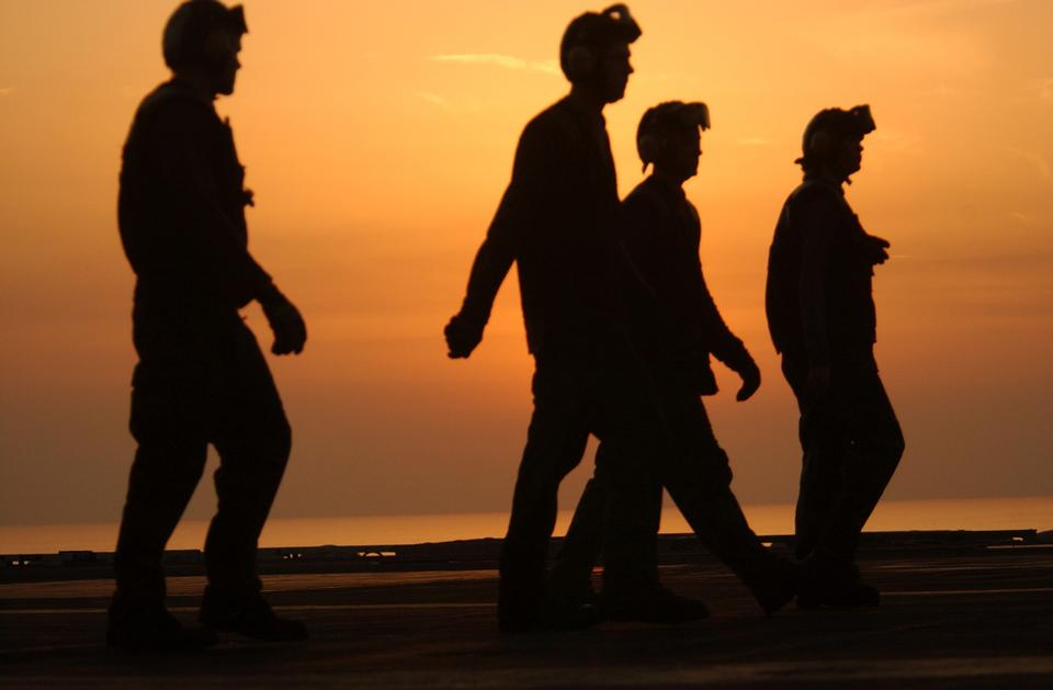 Free Crewmembers walk across the ships flight deck before the sun sets