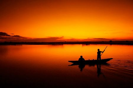 Free silhouette of fishermen with yellow and orange sun in the backgro