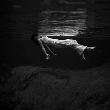 Free a woman, wearing a long gown, floating in water