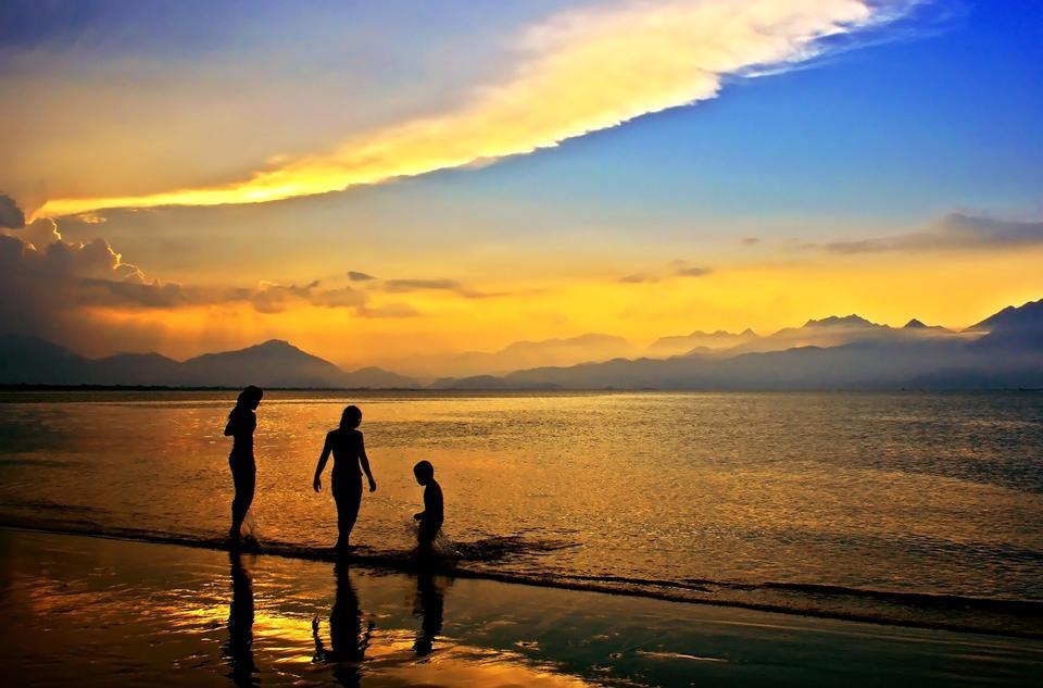 Free Young women walking on beach under sunset light