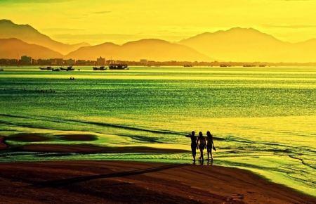 Free Women walk on the beach at sunset