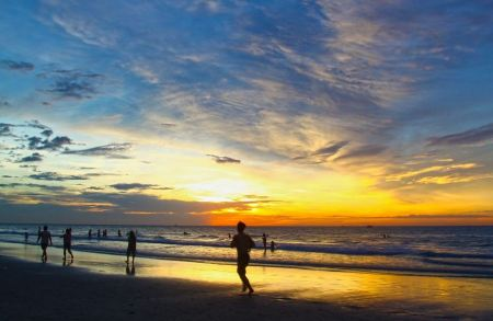 Free Young men jogging on wet sand by sea edge on vivid sunset