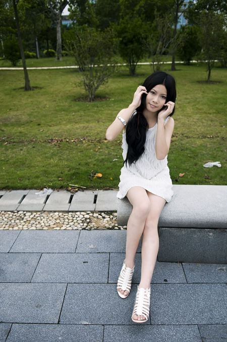 Free A Beautiful Chinese Girl Posing On A Bench Outdoors