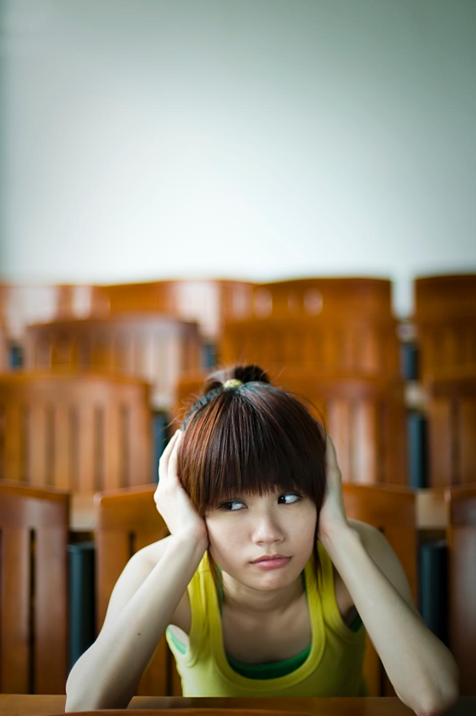 Free A Beautiful Chinese Girl Sitting Tired At A Desk
