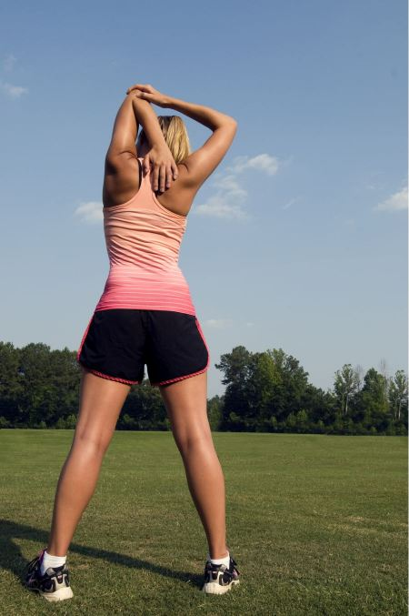 Free A Healthy Young Woman Stretching Before Exercise Outdoors