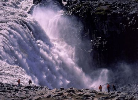 Free Tourist looking at the powerful waterfall of Dettifoss