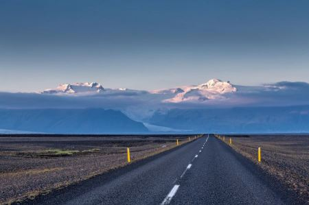 Free Empty road leading to snow covered mountains Iceland