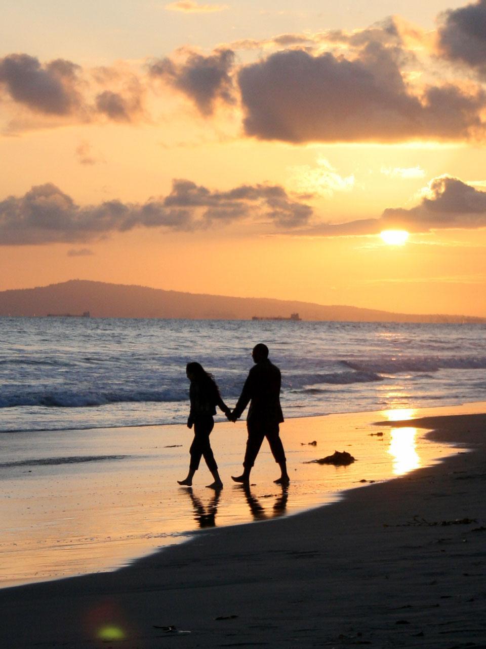 Free A couple strolls along Huntington Beach near sundown