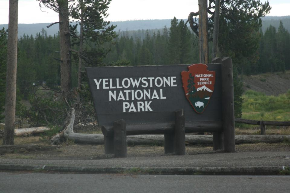 Free Road and Cars near a Yellowstone sign.