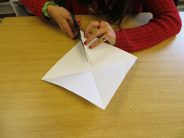 Free child's hands cutting paper scissors