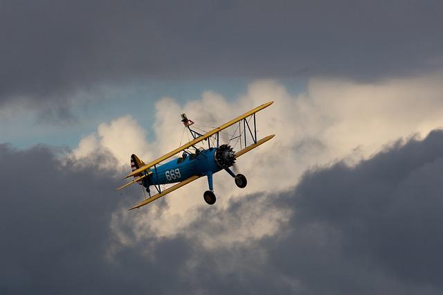 Free biplane flying propeller oldtimer heavy cloud