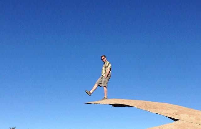 Free man balancing cool mountain hiking chip rock