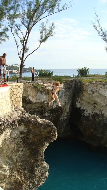 Free girl jumping water cliff diving high action