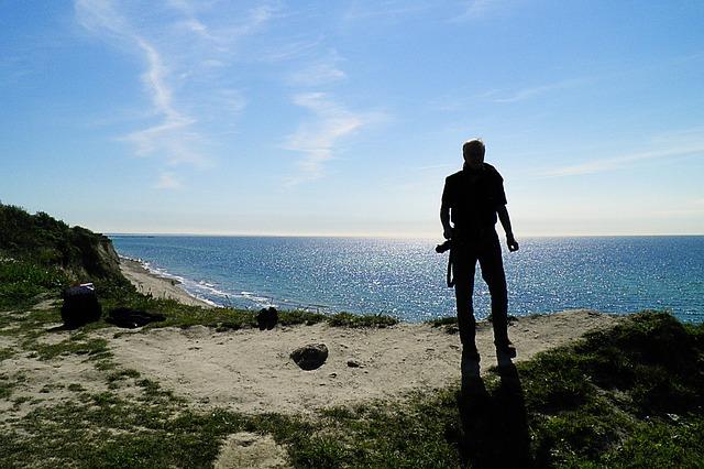 Free baltic sea coast back light man photographer darß